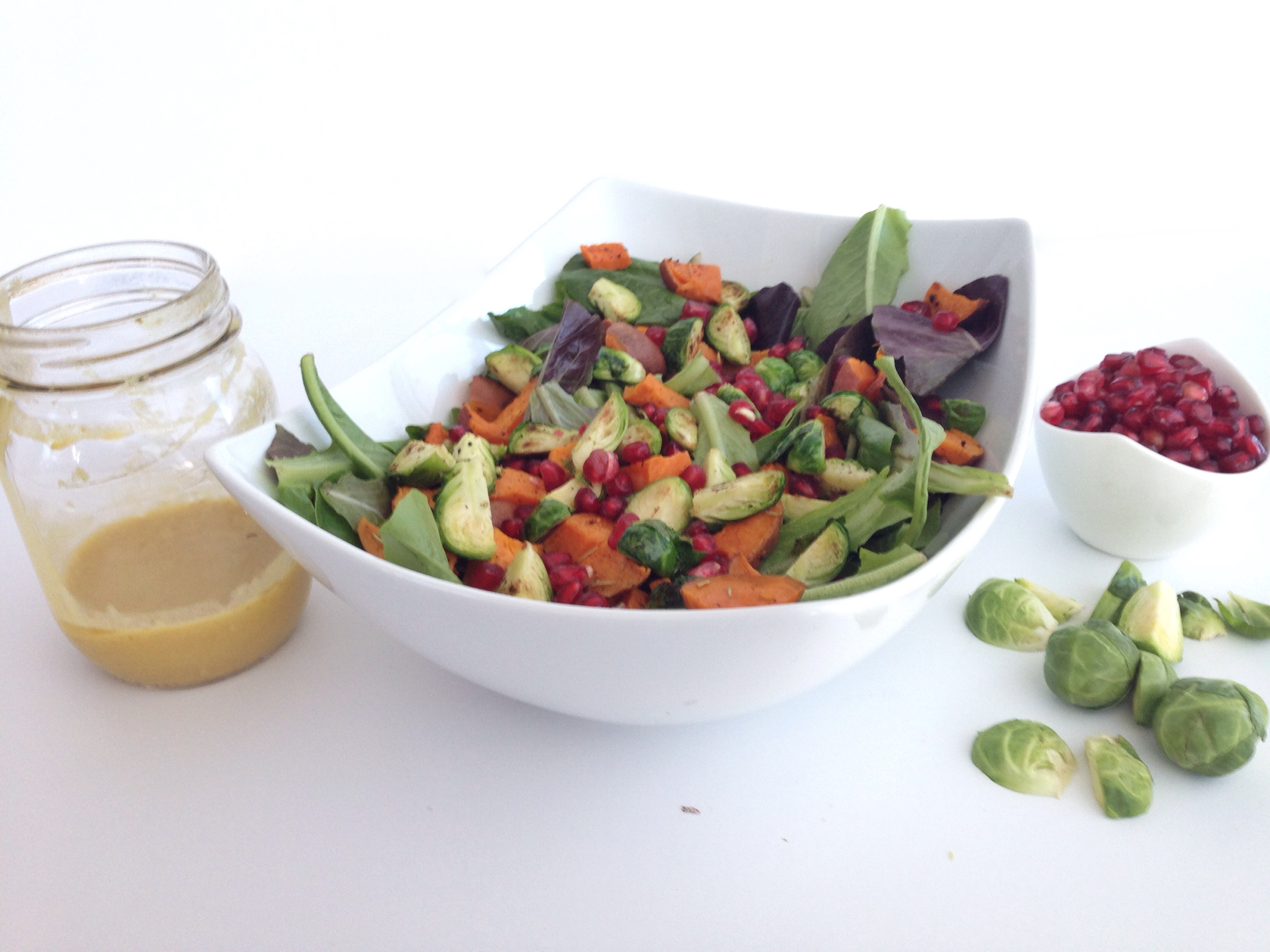 simple festive salad with dijon ginger dressing nourishing sweet potatoes brussels sprouts and pomegranate seeds